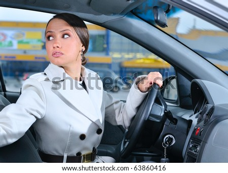 woman in a car is looking backwards trying to move back - stock photo