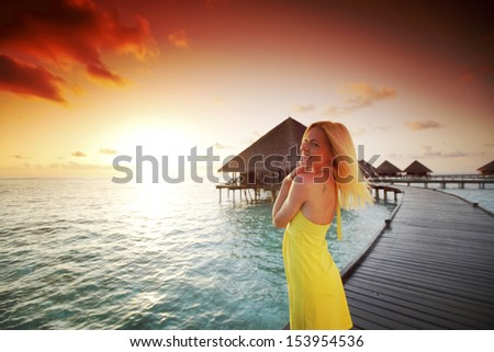 woman in a dress on a bridge home sea and the maldivian sunset on the background - stock photo