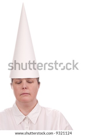 Woman in a dunce cap with eyes closed over a white background - stock photo