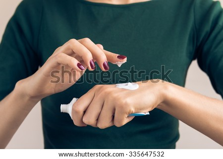 Woman in a green T-shirt and a maroon manicure using hand cream from a tube - stock photo