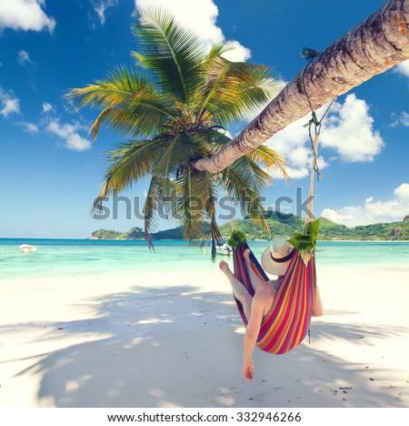 Woman in a hammock on a tropical beach - stock photo