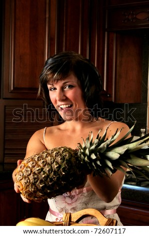 woman in a kitchen holding a pineapple to camera - stock photo