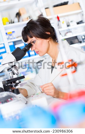 woman in a laboratory looking in a a microscope - stock photo