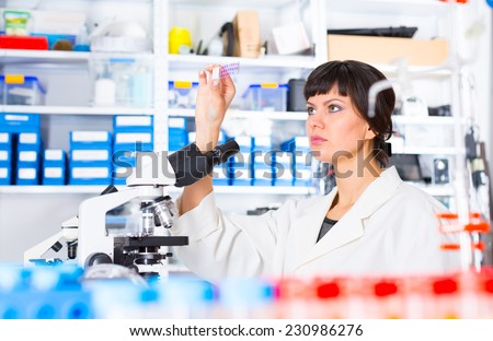 woman in a laboratory microscope with microscope slide in hand - stock photo