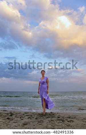 woman in a lilac dress on the beach