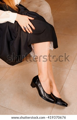 woman in a long black skirt shows classic shoes with heels