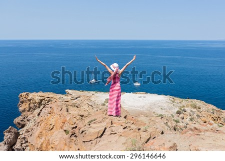 Woman in a long summer dress standing on a cliff and watches the ships at sea. Greece, Santorini. - stock photo