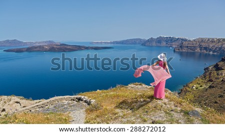 Woman in a long summer dress stands on the edge of a cliff, on the beach sea. Greece, Santorini - stock photo