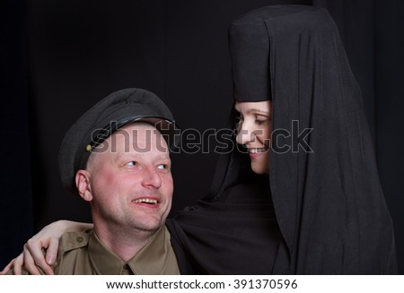 Woman in a monk robe and soldier on a black background. - stock photo