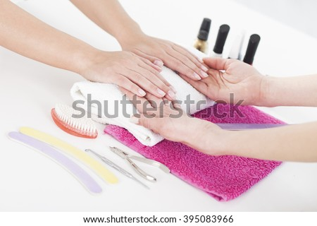 Woman in a nail salon receiving a manicure by a beautician.  - stock photo