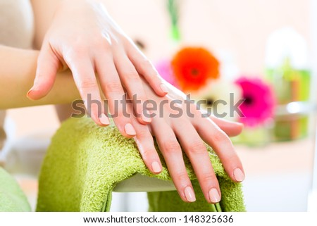 Woman in a nail salon receiving a manicure by a beautician, symbol picture with hands - stock photo