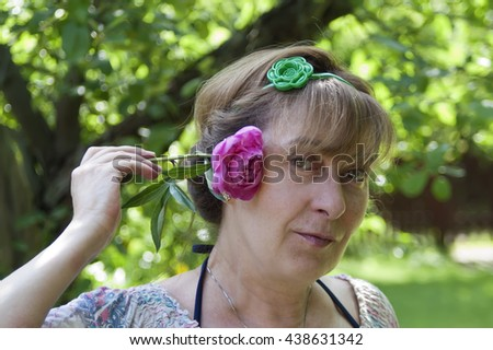 Woman in a playful mood holding a flower next to his head. A happy look on her face. Outdoor horizontal shot