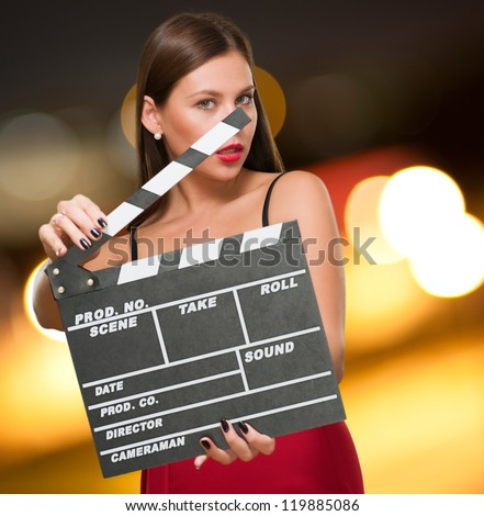 Woman In A Red Dress Holding Clapper Board against a city by night - stock photo