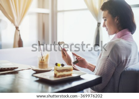 Woman in a restaurant holding digital tablet, browsing internet or connecting to wireless side view - stock photo