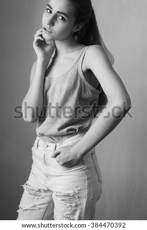 Woman in a shirt and torn jeans. Black and white.