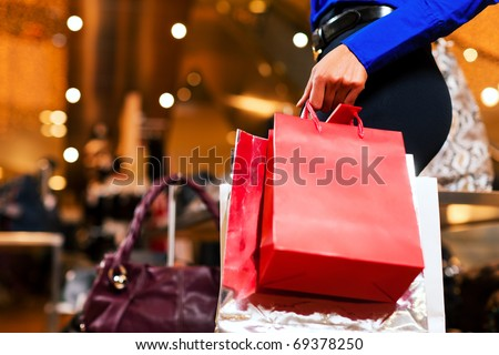 woman in a shopping mall with colorful bags