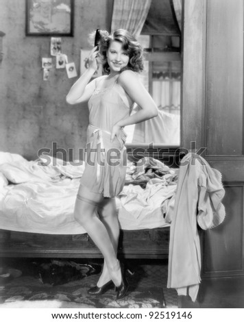 Woman in a slip and combing her hair posing sexily in her bedroom - stock photo