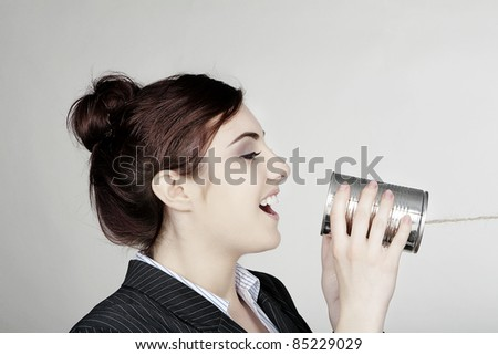 woman in a smart business suit in communication using a tin can and string - stock photo
