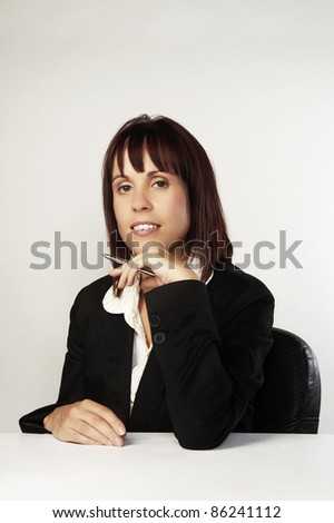 woman in a smart suit at her desk at work - stock photo