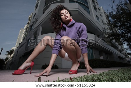 Woman in a squatting pose in the city