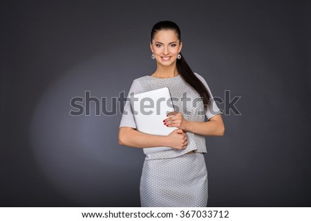 woman in a suit holding a laptop tablet in his hands and smiling - stock photo