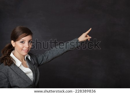 Woman in a suit indicate something on blackboard - stock photo