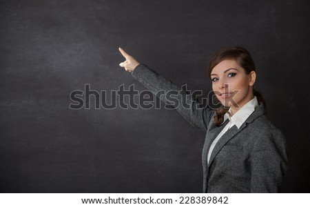 Woman in a suit indicate something on blackboard