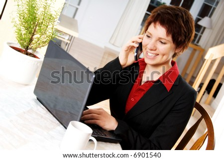 woman in a suit on the cell phone with laptop
