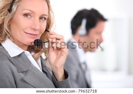 Woman in a suit using a headset with a male colleague in the background - stock photo