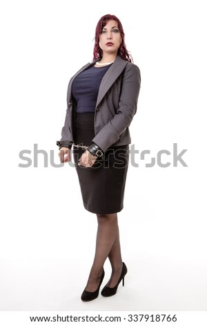 woman in a suit with her hands handcuffed at the front.