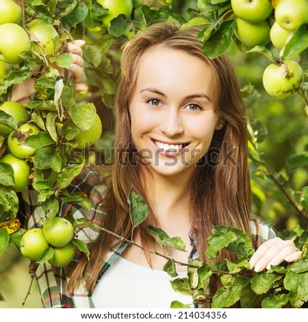 Woman in a sunny apple tree garden during the harvest season. Young smiling beautiful woman is standing among the sunlit apple trees with ripe organic apples on it. Healthy country lifestyle concept.  - stock photo