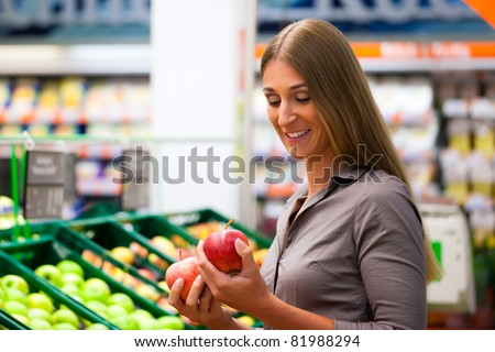 Woman in a supermarket at the shelf for fruits shopping for groceries, she is checking out the apples - stock photo