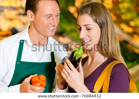 woman in a supermarket at the vegetable shelf shopping for groceries, a shop assistant is helping her - stock photo