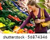 woman in a supermarket at the vegetable shelf shopping for groceries, she is choosing - stock photo