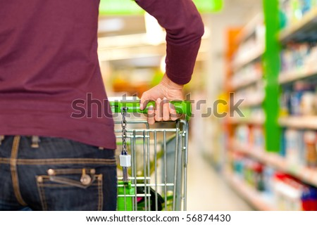 Woman in a supermarket running trough the aisle with a shopping cart - stock photo