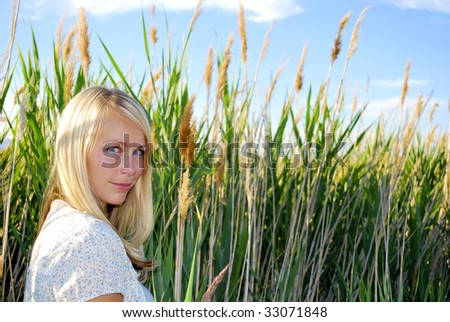 Woman in a tall field of grass - stock photo