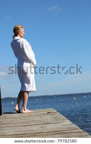 Woman in a toweling robe standing on a wooden jetty - stock photo