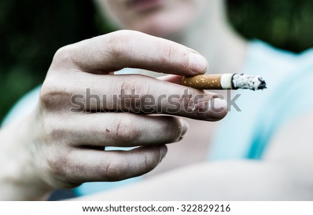 Woman in a very bad mood, holding in his hand, holding a smoldering between his fingers (fuming) cigarette. Cigarette close-up.  - stock photo