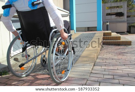 Woman in a wheelchair using a ramp - stock photo