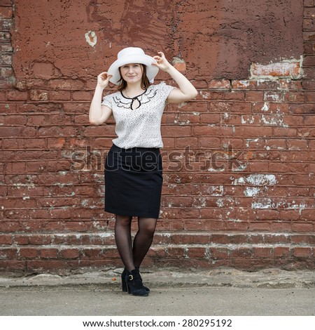Woman in a white hat, blouse and black skirt, standing against the backdrop of an old vintage brown brick wall. Model holds the edges of the hat by hand. Portrait of a woman in a retro style. - stock photo