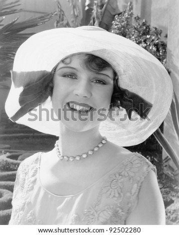 Woman in a wide brimmed hat smiling - stock photo