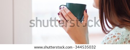 woman in a window with a cup of tea on her hands - stock photo