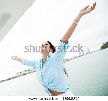 Woman in a yacht with arms open enjoying her freedom