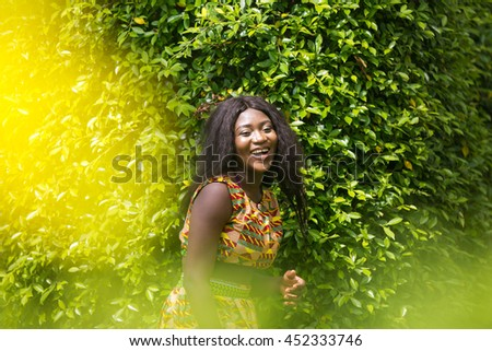 Woman in African-print dress in a garden.
