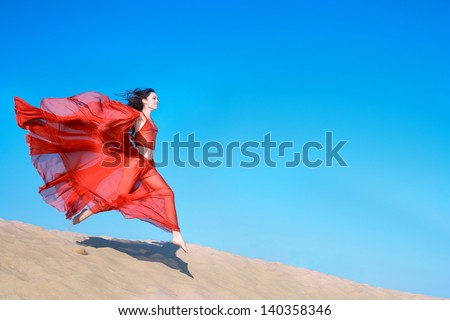 Woman in airy red dress running on sand dunes