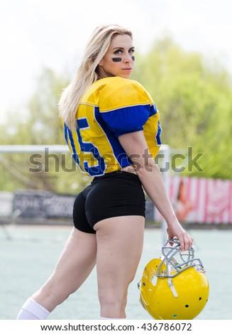 Woman in american football equipment on the stadium - stock photo