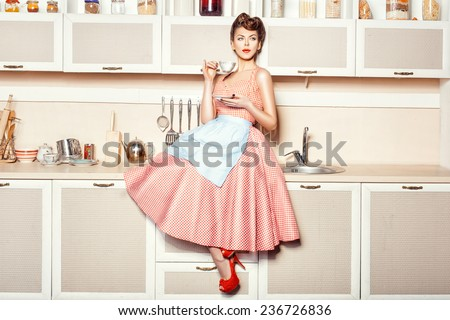 Woman in an apron in the kitchen drinking from a cup sitting on the table. - stock photo