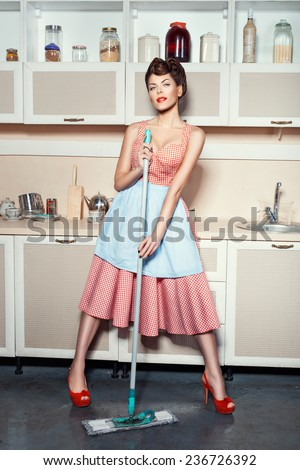 Woman in an apron washing floors in the kitchen.