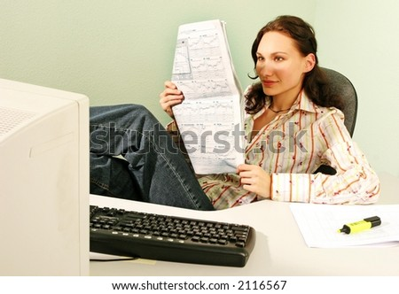 woman in an office reading business statistics of a stock market