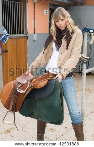 Woman in an stable with jeans and a horse - stock photo